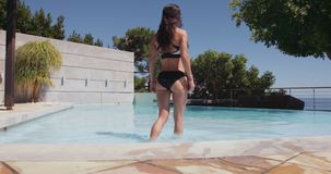 Beautiful young woman walking into the pool stock video