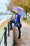Beautiful young woman walking beside river on rainy autumn day Royalty Free Stock Photo