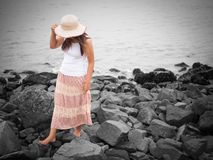 Beautiful young woman walking on the rock beach near the sea. walk away concept.  Royalty Free Stock Photography