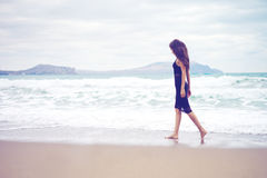 Beautiful young woman walking at the sea Stock Image