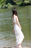 Beautiful young woman walking on the side of a river Stock Image