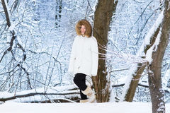 Beautiful young woman walking in a snowy park Stock Images
