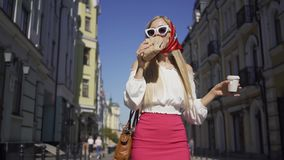 Beautiful young woman walking on the street drinking coffee and eating croissant. Attractive fashionable girl enjoying stock video