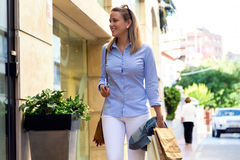 Beautiful young woman walking in the street. Shopping concept. Stock Images
