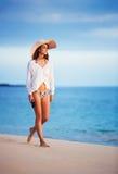 Beautiful young woman walking on tropical beach. Vacation Resort Lifestyle. Beautiful young woman walking on tropical beach Royalty Free Stock Photos