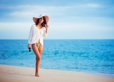 Beautiful young woman walking on tropical beach. Vacation Resort Lifestyle. Beautiful young woman walking on tropical beach Royalty Free Stock Images