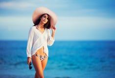 Beautiful young woman walking on tropical beach. Vacation Resort Lifestyle. Beautiful young woman walking on tropical beach Stock Images