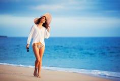 Beautiful young woman walking on tropical beach. Vacation Resort Lifestyle. Beautiful young woman walking on tropical beach Royalty Free Stock Image