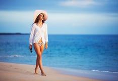 Beautiful young woman walking on tropical beach. Vacation Resort Lifestyle. Beautiful young woman walking on tropical beach Stock Photography