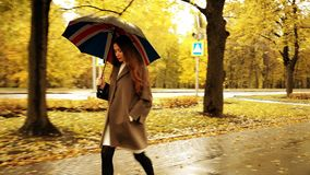 Beautiful young woman walking with umbrella along autumn alley on a rainy day. Beautiful young woman walking along autumn alley Stock Photos