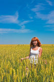 Beautiful young woman walking at wheat field Royalty Free Stock Image