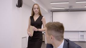 Beautiful young woman walks through office and joins company at the desk. stock footage