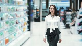 Beautiful young woman walks through sales area in cosmetics shop, slow motion. Concept of purchases, shopping stock footage