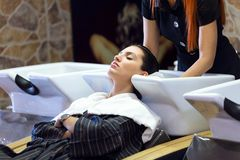 Beautiful young woman washes hair in a beauty salon. Portrait of beautiful young woman washes hair in a beauty salon Royalty Free Stock Image