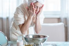 Beautiful young woman washing and refreshing face with water in the morning. Concept of hygiene and care for the skin stock image