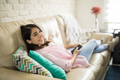 Beautiful young woman watching television Stock Photography