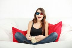 Beautiful young woman watching TV in 3d glasses Royalty Free Stock Photography
