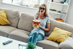 Beautiful young woman watching TV. In 3-D glasses and eating popcorn while relaxing on the sofa at home stock photos