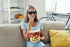 Beautiful young woman watching TV in 3-D. Glasses and eating popcorn while relaxing on the sofa at home royalty free stock photo
