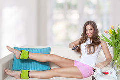 Beautiful young woman watching tv while doing leg exercises Royalty Free Stock Image