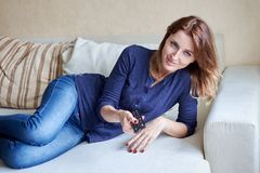 Beautiful young woman watching tv on sofa at home Royalty Free Stock Photos