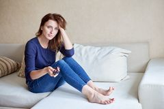 Beautiful young woman watching tv on sofa at home Stock Images