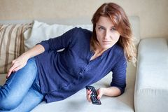 Beautiful young woman watching tv on sofa at home Stock Photo