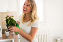 Beautiful young woman watering and caring for flowers Stock Photo