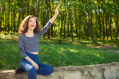 Beautiful young woman waves hand to somebody. While sitting outdoors in park Stock Images