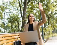 Beautiful young woman wearing autumn coat using laptop royalty free stock images