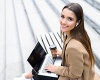 Beautiful young woman wearing autumn coat using laptop stock images