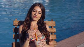 Beautiful young woman wearing bikini drinking cocktail, sitting by the pool and sunbathing stock footage