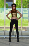 Beautiful young woman wearing black hat, gold top and black jeans modeling. Nineteen`s style. Fashion photo shoot. Stock Photo