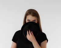 Beautiful young woman wearing black hat on light background. No face Royalty Free Stock Photo