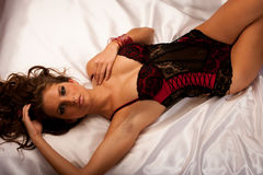 Beautiful young woman wearing black and red lingerie in bed Royalty Free Stock Images