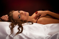 Beautiful young woman wearing black and red lingerie in bed Stock Photography