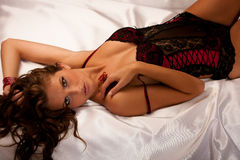 Beautiful young woman wearing black and red lingerie in bed Stock Images