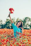 Young woman walking with bouquet in poppy meadow. Beautiful young woman wearing in blue dress walking with bouquet in red poppy meadow royalty free stock photography