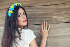 Beautiful young woman wearing blue and yellow wreath against woo Royalty Free Stock Images