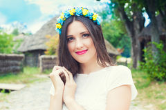 Beautiful young woman wearing blue and yellow wreath and posing Royalty Free Stock Photography