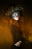 Beautiful young woman wearing carnival mask with feathers Stock Photo