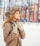 Beautiful young woman wearing a coat and hat over snow in winter day Stock Photos
