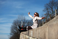 Beautiful young woman wearing a coat on a sunny winter day. Blonde girl with sunglasses dreams about flying in front of blue sky Royalty Free Stock Image