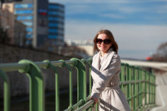 Beautiful young woman wearing a coat on a sunny winter day. Blonde girl with sunglasses leaning on a handrail stock photos