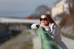 Beautiful young woman wearing a coat on a sunny winter day. Blonde girl with sunglasses leaning on a handrail royalty free stock photos