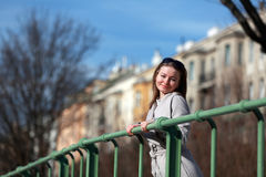 Beautiful young woman wearing a coat on a sunny winter day. Blonde girl with sunglasses leaning on a handrail stock photo