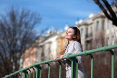 Beautiful young woman wearing a coat on a sunny winter day. Blonde girl with sunglasses leaning on a handrail stock image