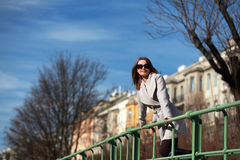 Beautiful young woman wearing a coat on a sunny winter day. Blonde girl with sunglasses leaning on a handrail royalty free stock images