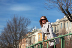 Beautiful young woman wearing a coat on a sunny winter day. Blonde girl with sunglasses leaning on a handrail Royalty Free Stock Photo