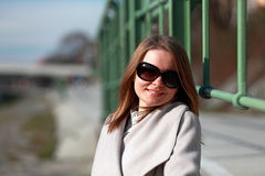 Beautiful young woman wearing a coat on a sunny winter day. Blonde girl with sunglasses leaning on a handrail Stock Images